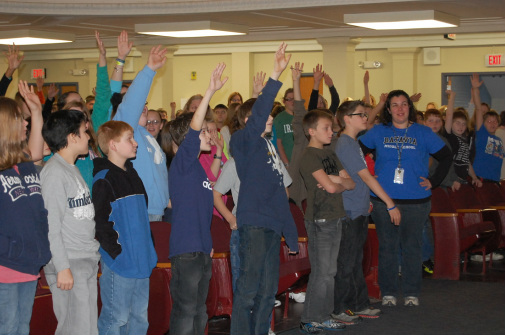 Students raising their hands in response to Andy's presentation