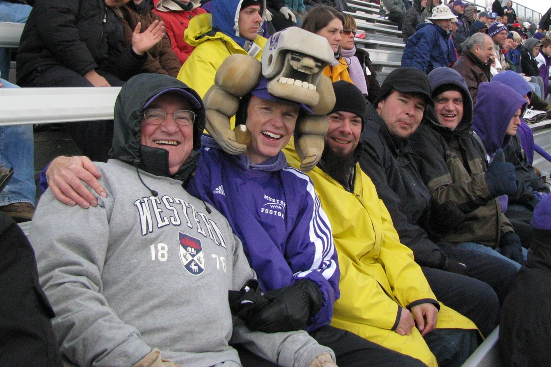 Andy at university football game with dad and brother
